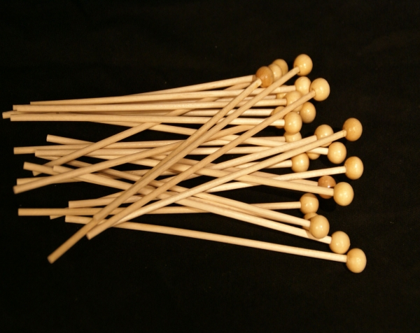Pile of small wood diameter dowels with ball tops on one end. Dowels that have ball tops can be used for lollipop sticks, candy sticks, or rock candy sticks.