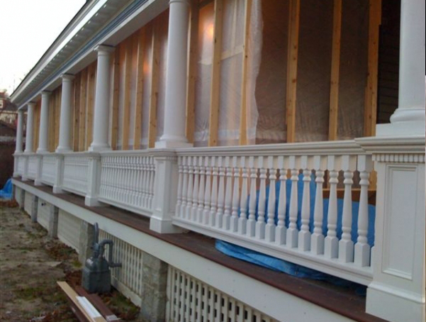 View of porch with turned white wood balusters and columns and square newels.
